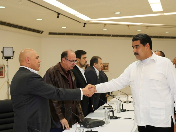 Presidente venezuelano, Nicolas Maduro, aperta a mão de Jesus Torrealba, secretário da coalizão dos partidos de oposição, durante encontro em Caracas, no domingo (30) (Foto: Miraflores Palace via Reuters)