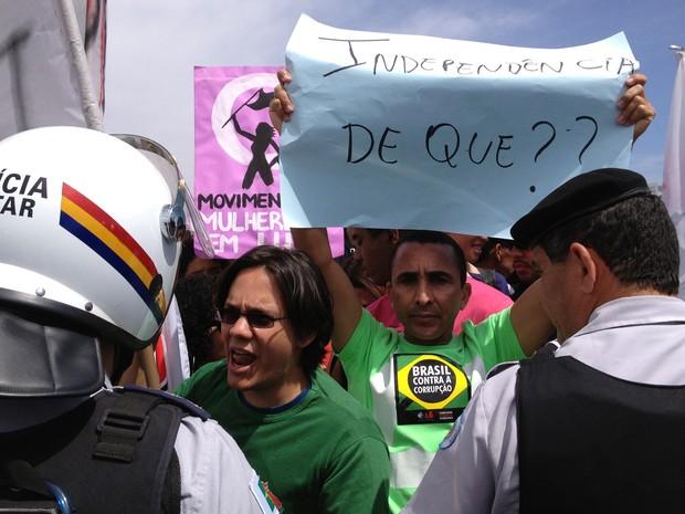 Manifestante ergue cartaz diante de policiais na Marcha Contra a Corrupção em Brasília (Foto: Felipe Néri / G1)