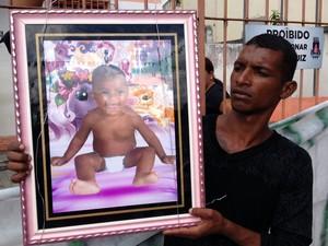 Morador exibe foto da criança que foi morta após ação da polícia (Foto: Ruan Melo/G1)