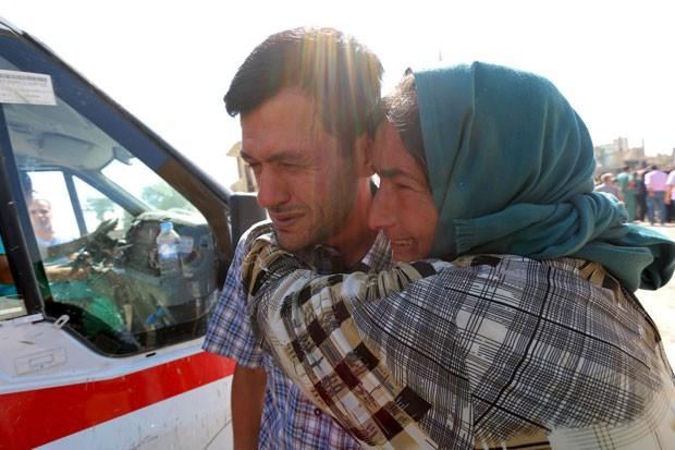 Abdullah Kurdi, que perdeu os dois filhos e a mulher em um naufrágio na Turquia, chora abraçado a um parente durante o funeral de sua família em Kobane, na Síria, nesta sexta-feira (4) (Foto: Rodi Said/Reuters)
