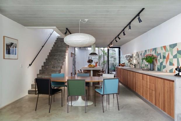 Integrada à sala de jantar, a área com ilha de concreto aparente é fechada por painéis de vidro articulado da Solarlux para o pátio interno. Ao fundo, a área de serviço tem porta de metal perfurado (Foto: Alessandro Guimarães / Divulgação)