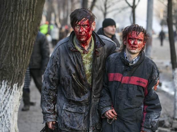 18/2 - Feridos no confronto com a polícia caminham abraçados em Kiev (Foto: Vlad Sodel/Reuters)
