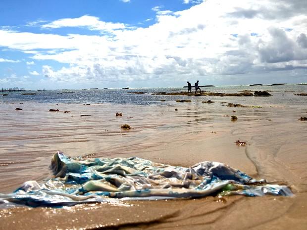 Espécie de fralda descartavél é abandonada em praia (Foto: Waldson Costa / G1)