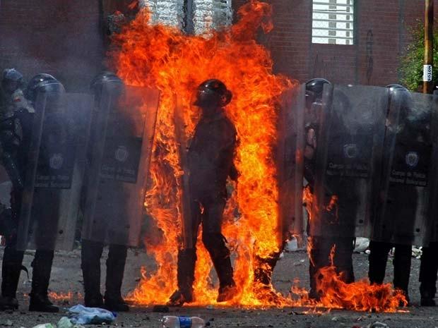 Policial é incendiado duratne protesto em San Cristobal nesta segunda-feira (25) (Foto: AFP PHOTO/GEORGE CASTELLANOS)