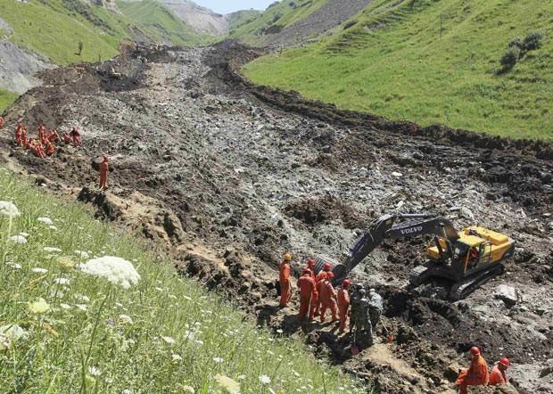 Equipes com escavadeiras buscam vítimas nesta terça-feira (31) após deslizamento em mina na China (Foto: AFP)