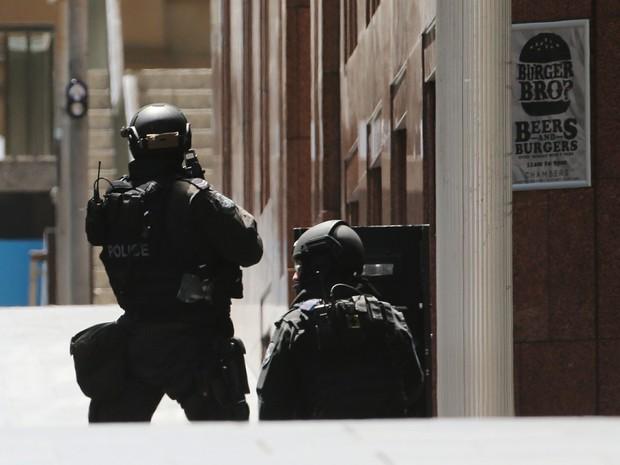 Policiais cercam área onde está localizado café invadido por um homem armado na Austrália (Foto: Rob Griffith/AP Photo)