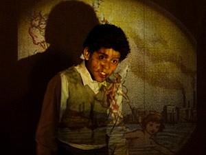 Elias fica admirado com a lanterna mágica (Foto: Lado a Lado / TV Globo)