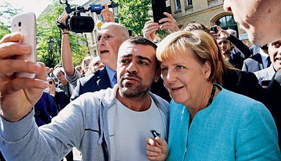 Angela Merkel posa para foto com refugiado em um centro em Berlim (Foto: Fabrizio Bensch/Reuters)