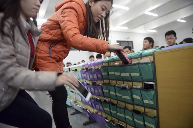 Alunas colocam dispositivos em 'porta-celular coletivo' em universidade na China (Foto: AP)