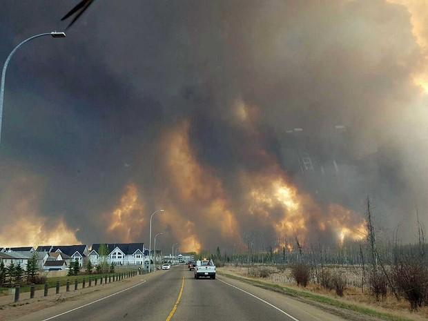 Imagem do imenso incêndio florestal visto de uma estrada perto de Fort McMurray (Foto: Mary Anne Sexsmith-Segato / The Canadian Press / via AP Photo)