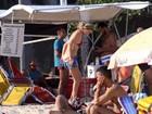 Letícia Birkheuer se descuida e mostra demais em praia com o filho
