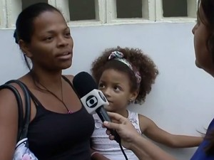 Moradora de Vila Laura chegou cedo a posto de saúde para vacinar filha (Foto: Imagens / TV Bahia)