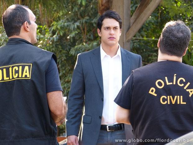 Hélio recebe intimação da polícia e não consegue fugir (Foto: Flor do Caribe / TV Globo)