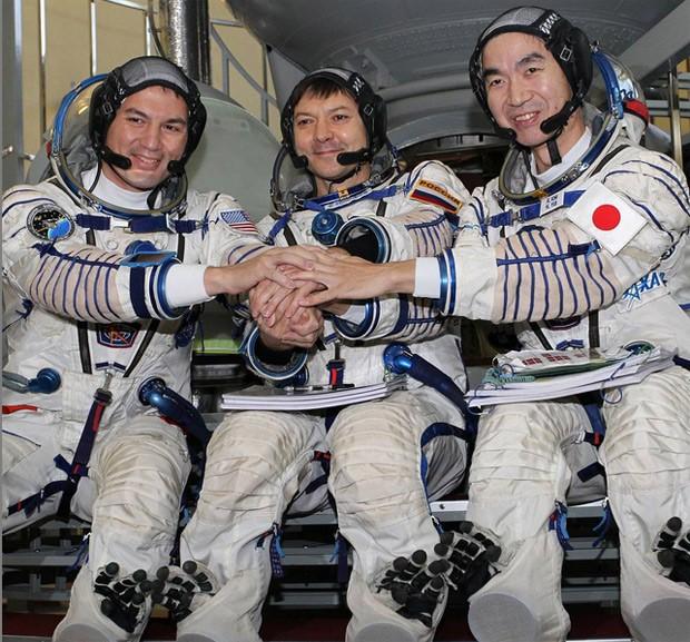 Astronautas Kjell Lindgren, da Nasa, Oleg Kononenko, da Roscosmos, e Kimiya Yui, da Jaxa, posam para foto em frente a simulador do foguete Soyuz  (Foto: Reprodução/Instagram/ISS)