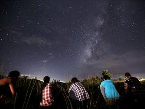 Jovens observam o céu perto de Yangon, Mianmar, para ver meteoros na segunda (12) (Foto: Ye Aung Thu/AFP)