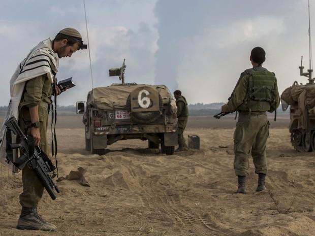 29/7 - Soldado israelense faz oração perto da fronteira de Israel com Gaza, com fumaça de ataques vista ao fundo (Foto: Jack Guez/AFP)