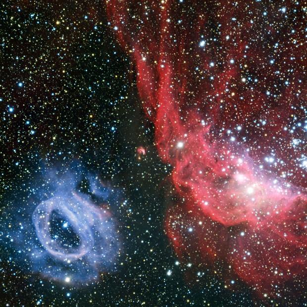 Imagem mostra duas nebulosas de gás brilhante, uma avermelhada e outra azul (Foto: ESO)