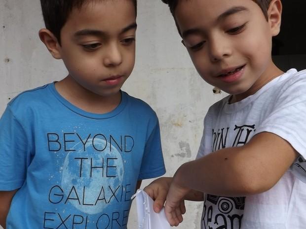 Guilherme (azul) e Gustavo (branco) brincam com uma 'formiguinha' (Foto: Caio Gomes Silveira/ G1)