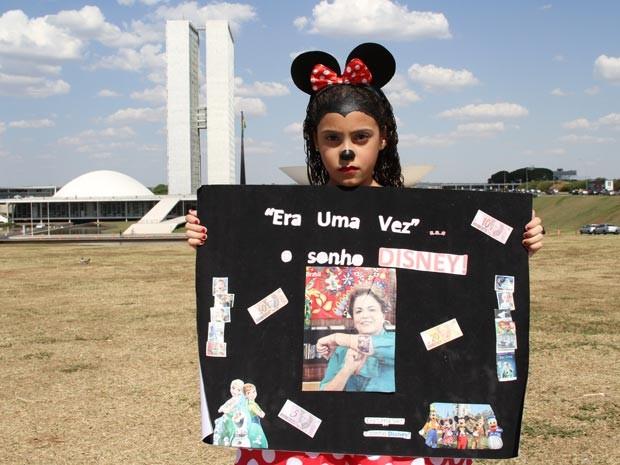 Maria Rita vestida de MInnie e com cartaz de protesto contra a alta do dólar, que fez com que pai adiassem viagem aos EUA (Foto: Vianey Bentes/TV Globo)