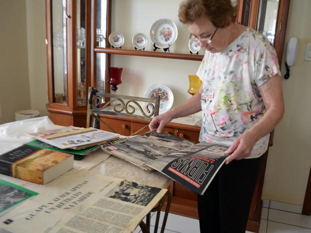 Dona Esmeralda folheia publicações da época da inundação de Guapé por reservatório de Furnas (Foto: Samantha Silva / G1)