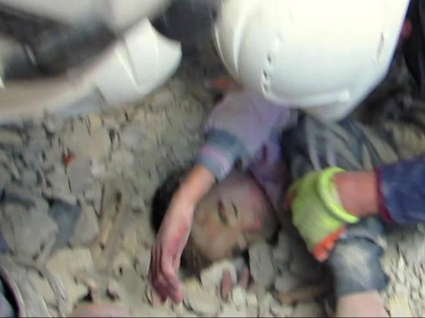 Criança é desenterrada com vida de escombros após ataque na Síria (Foto: Reprodução/ BBC)