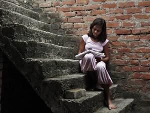 Sushma estuda em uma escada que dá acesso ao apartamento onde mora (Foto: Rajesh Kumar Singh/AP)