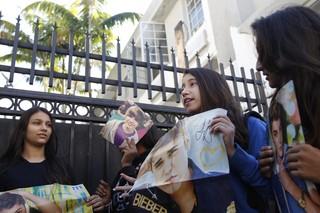 Fãs seguram cartazes de Justin Bieber na porta do hotel onde ele estaria hospedado em Miami (Foto: Reuters)
