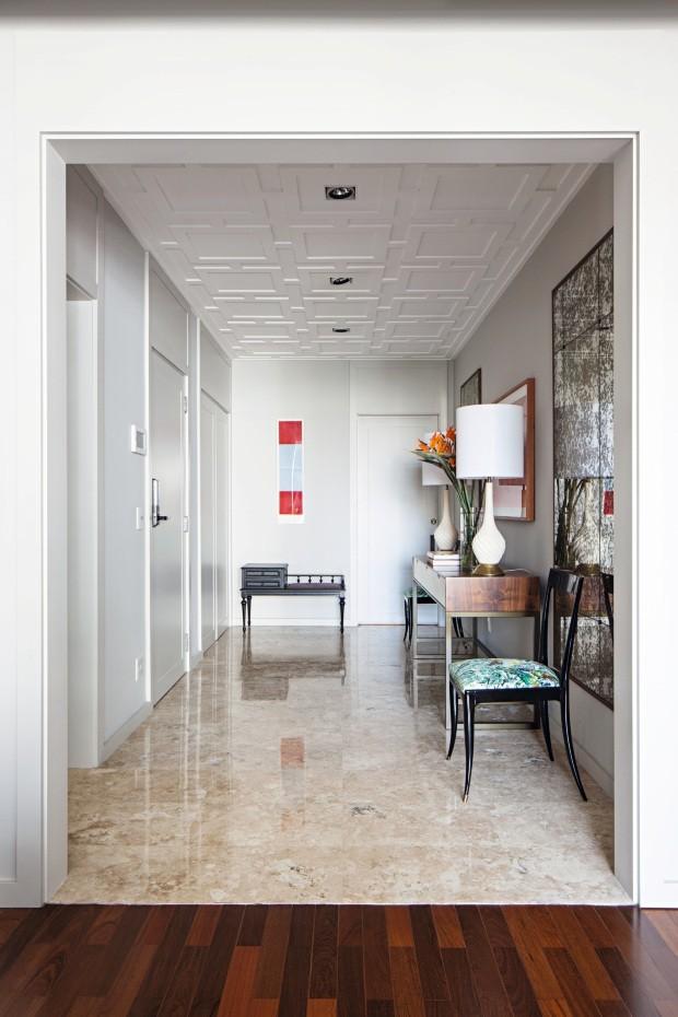 O piso de mármore travertino foi restaurado e o teto recebeu gesso com desenho proposto pelo escritório. Ao fundo, sob a obra de Renata Tassinari, na Galeria Pilar, há um antigo banco reciclado (Foto: Gui Morelli / Divulgação)