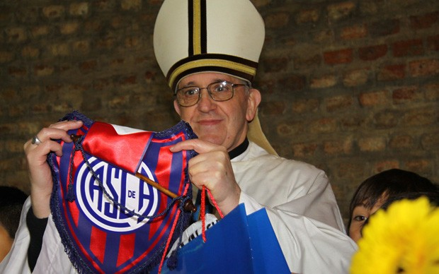 O então cardeal Jorge Mario Bergoglio posa para foto segurando uma flâmula do seu time (Foto: Club Atlético San Lorenzo de Almagro/AP)