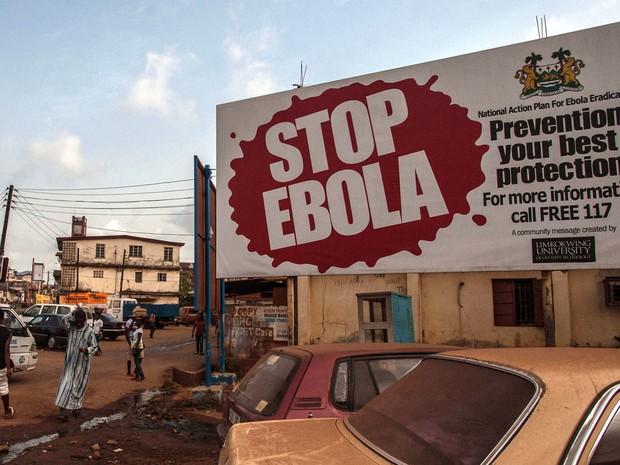 Pessoas passam por outdoor com alerta sobre o ebola na cidade de Freetown, em Serra Leoa, na sexta (15) (Foto: AP Photo/Aurelie Marrier d'Unienville)