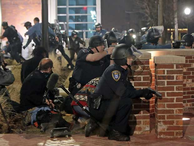 Policiais se protegem durante tiroteio em Ferguson. (Foto: St. Louis Post-Dispatch / Laurie Skrivan / Via AP Photo)