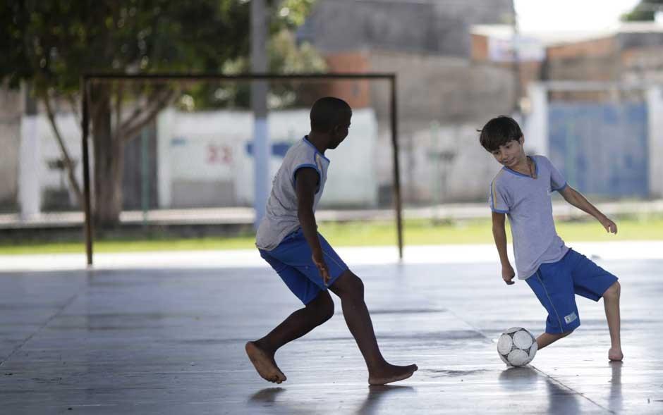 O menino Gabriel Muniz, de 11 anos de idade, joga futebol com um amigo em sua escola em Campos dos Goytacazes, no Rio de Janeiro. Ele nasceu com má formação nos pés, mas sonha ser um jogador profissional quando crescer - como seu ídolo, Lionel Messi. (Foto: Ricardo Moraes/Reuters)