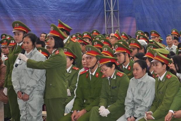 Cercados por policiais, acusados são julgados por tráfico de drogas nesta segunda-feira (20) em Quang Ninh, no Vietnã (Foto: AFP)