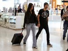Com cara de poucos amigos, Alinne Moraes viaja com o namorado