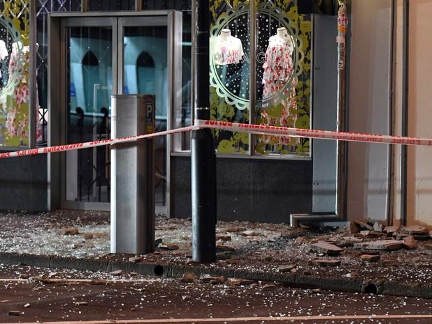 Estilhaços de vidro e pedaços de alvenaria são vistos em calçada em frente a loja em Wellington (Foto: Ross Setford/SNPA via AP)