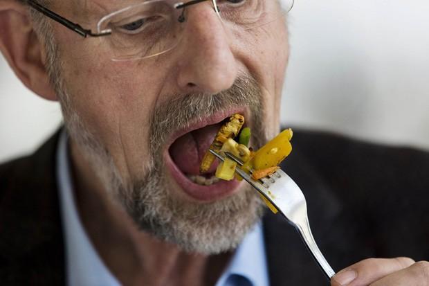 Professor Arnold van Huis come prato frito feito com vegetais, larvas e gafanhotos na Holanda (Foto: Michael Kooren/Reuters)