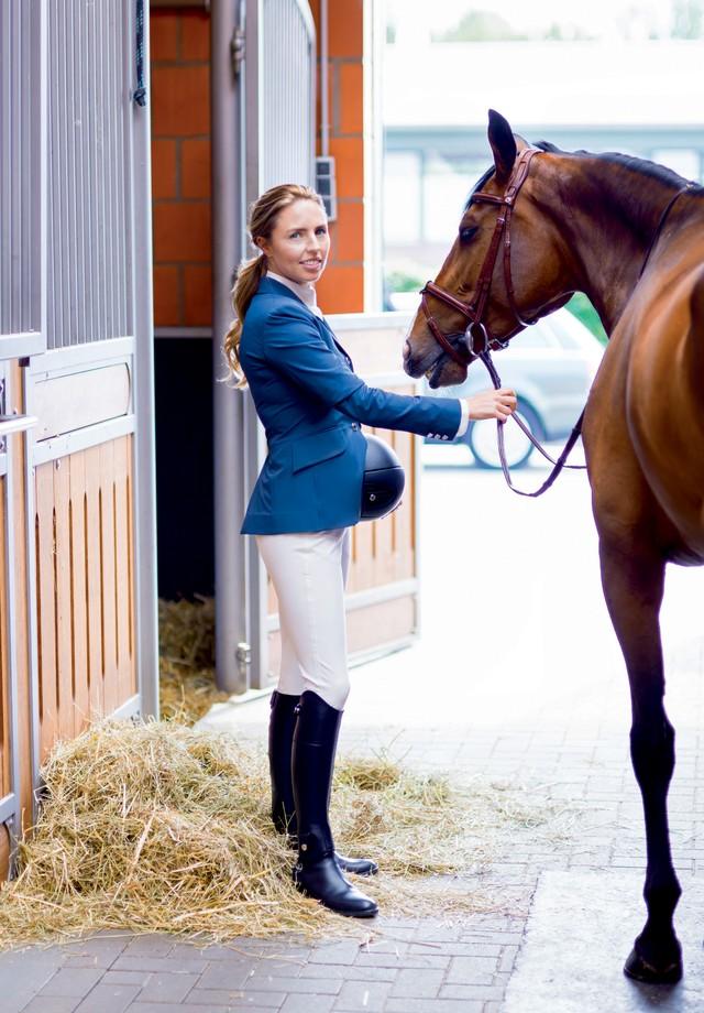 Karina posa nas cocheiras de seus cavalos em Münster, na Alemanha, vestindo culotes (R$ 4.700), blazer (R$ 9.150), camisa (R$ 2.325), casquete (R$ 4.200) e botas (R$ 5.970). No cavalo, rédea de couro (R$ 3.900).   (Foto: Peter Rigaud)
