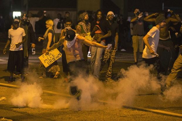 Manifestante chuta lata de gás lacrimogêneo atirada pela polícia durante protestos em Ferguson, no Missouri, neste domingo (17) (Foto: Lucas Jackson/Reuters)