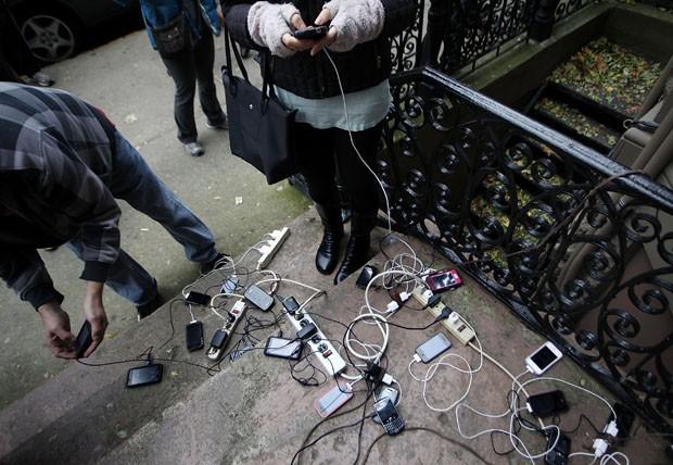 Pedestres carregam celulares em tomada oferecida por uma casa (Foto: Jeff Zelevansky/Getty Images/AFP)