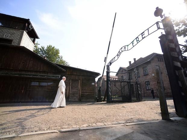 O Papa Francisco caminha em direção à entrada do campo de extermínio nazista de Auschwitz, com a frase 'Arbeit Macht Frei' ('O trabalho liberta', em alemão), em Oswiecim, na Polônia, como parte da programação da Jornada Mundial da Juventude (Foto: Filippo Monteforte/AFP)