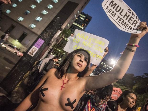 Mulher de topless com os mamilos cobertos ergue cartaz com a frase 'Ser mulher sem temer' no protesto 'Por Todas Elas', contra a cultura do estupro e a violência praticada contra as mulheres, na Avenida Paulista, em São Paulo (Foto: Cris Faga/Fox Press Photo/Estadão Conteúdo)