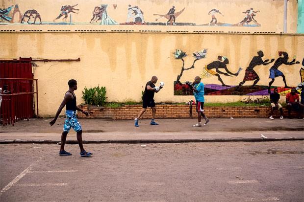 No portão do estádio Tata Raphael, homens simulam uma luta imaginária (Foto: Yan Boechat)