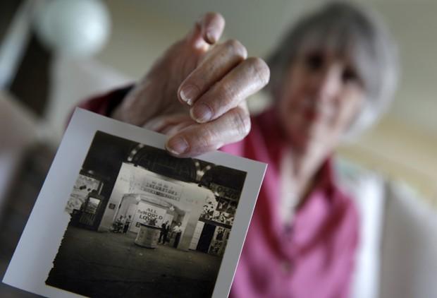 Beth Allen mostra uma foto feita por seu pai da entrada da exposição de bebê prematuros em incubadoras (Foto: Mel Evans/ AP)