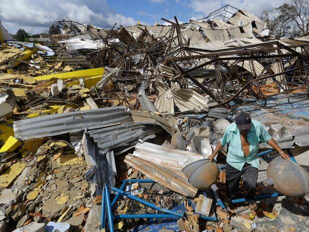 Homem retira holofotes de um ginásio destruído após passagem do tornado pela cidade de Xanxerê, em Santa Catarina, no começo da semana. Duas pessoas morreram, 15 ficaram feridas e mais de mil estão desabrigadas  (Foto: Nelson Antoine/Frame/Estadão Conteúdo)