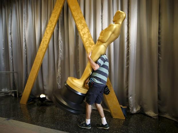 Homem carrega uma estátua até a entrada do Dolby Theatre, onde serão conhecidos os vencedores do Oscar 2016 (Foto: Lucy Nicholson / Reuters)