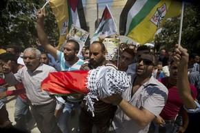 Palestinos carregam o corpo do menino de 1 ano e meio que morreu durante um incêndio em sua casa em Duma, na Cisjordânia, nesta sexta-feira (31) (Foto: Majdi Mohammed/AP)