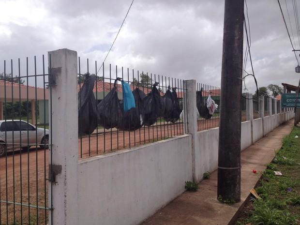 Sacolas com lixo estão penduradas na grade de prédio da prefeitura (Foto: Dyepeson Martins/G1)