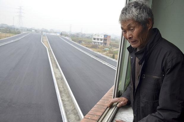Idoso observa da janela estrada contornando sua casa. (Foto: China Daily/Reuters)
