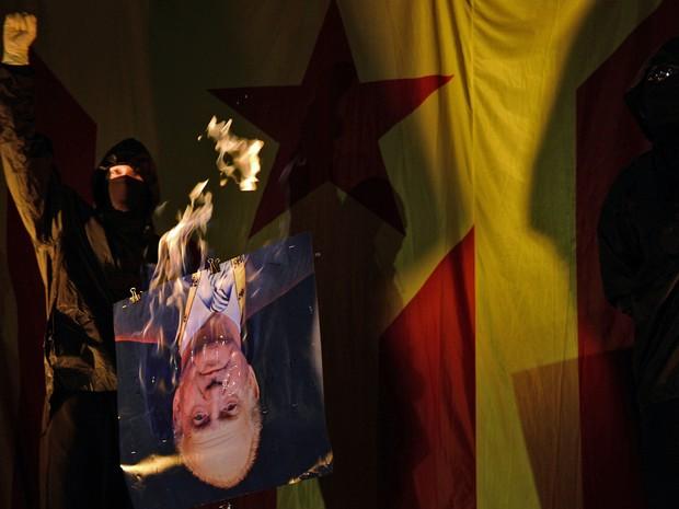 Um membro do partido radical independentista catalão queima uma imagem do rei da Espanha Juan Carlos, durante o Dia Nacional de Catalunha, em Barcelona. (Foto: Lluis Gene/AFP)