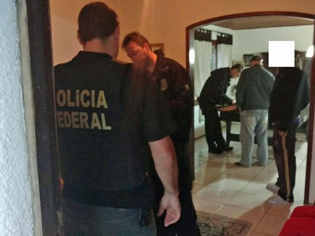 Policiais federais cumprem mandado durante operação para combater organização criminosa que prometia fraudar eleições (Foto: Polícia Federal/Divulgação)